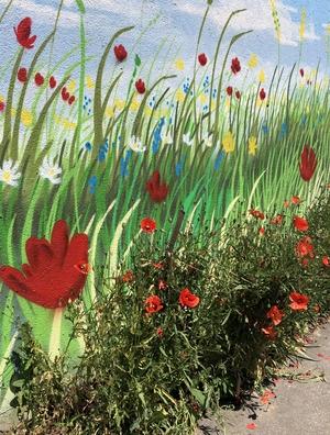 Malerei von Mohn und anderen Blumen auf einer Garagenwand